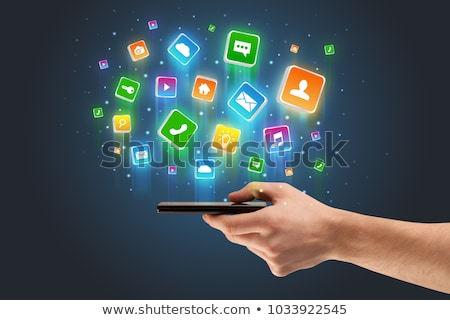 Hand using phone with application icons flying around Stock photo © ra2studio