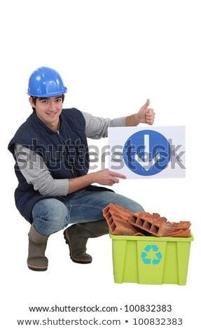 Stock photo: Tradesman holding a sign pointing to a recycling bin