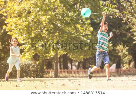 Laughing boy chasing a balloon Stock photo © konradbak