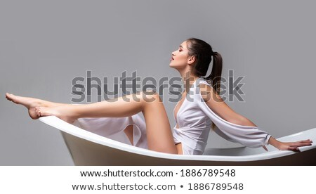 woman in shower washes. Beautiful long legged girl in bath Stock photo © popaukropa