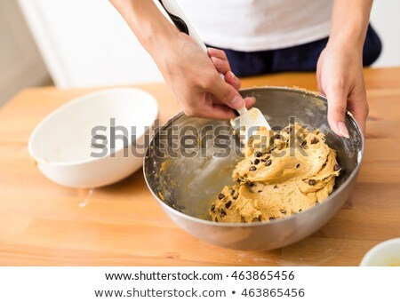 Woman adding chocolate chips into the dough Stock photo © wavebreak_media