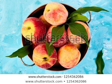 Ripe peaches in a bowl, basket on the blue table. Stock photo © Illia