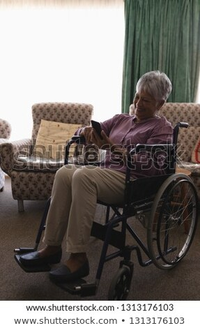 Front view of disabled  happy senior woman using mobile phone in living room at home Stock photo © wavebreak_media