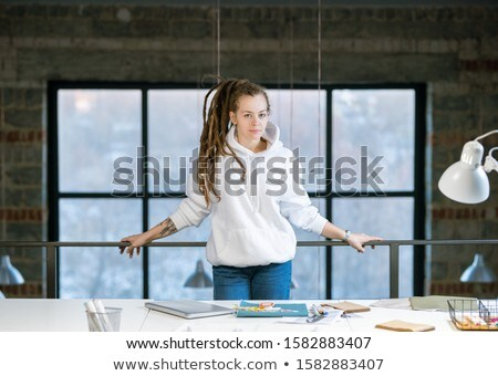 Pretty young creative designer in white hoodie and blue jeans standing in studio Stock photo © pressmaster