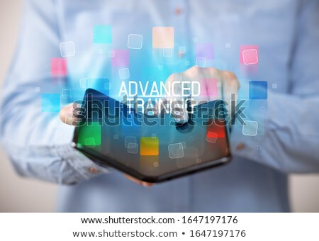 Young man holding a foldable smartphone Stock photo © ra2studio