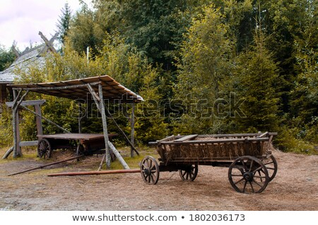Two old wooden cartwheel against wood cart Stock photo © backyardproductions