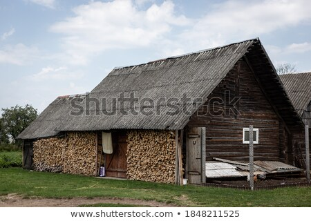 wood stacked against a farm wall stock photo © morrbyte
