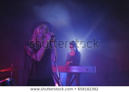 smiling musician playing piano in illuminated nightclub stock photo © wavebreak_media