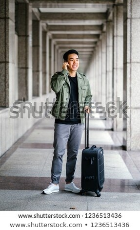 Asian man with suitcase talking on phone Stock photo © studioworkstock