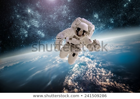 Сток-фото: Astronaut In Outer Space Against The Backdrop Of The Planet Eart