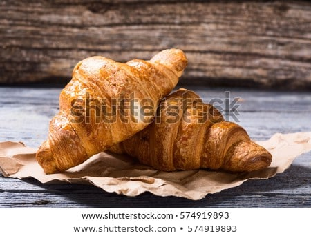 Tasty buttery croissants on old wooden table Stock photo © boggy