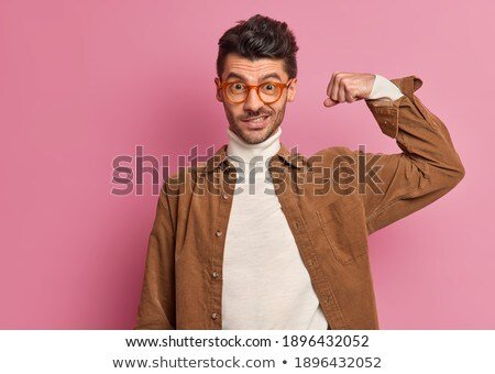 Young handsome fitness man in pink shirt, studio shot. Stock photo © Lopolo