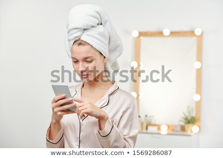 Young clean woman in silk pajamas scrolling through messages in smartphone Stock photo © pressmaster