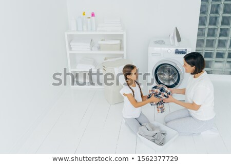 Little girl helper and her mother pose in laundry room near washing machine, sit on white floor, hol Stock photo © vkstudio