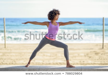 Young sporty woman doing yoga asana Warrior I Pose outdoors under industrial bridge Stock photo © GVS