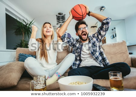Stock photo: Smiling couple watching a sports in television