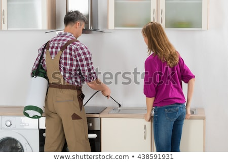 Woman And Worker Spraying Pesticide In Kitchen Stock photo © AndreyPopov