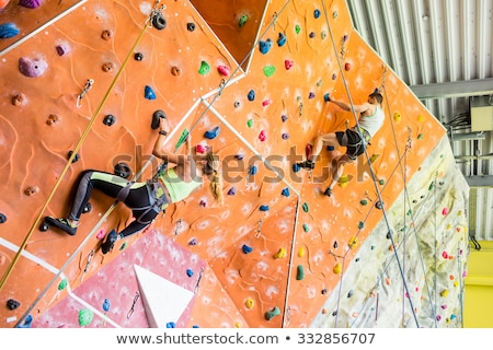 man and woman climbing a wall at indoor gym Stock photo © dolgachov
