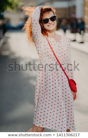 Mirthful young lady strolls on street, has long red hair, wears stylish dress, sunglasses, enjoys su Stock photo © vkstudio
