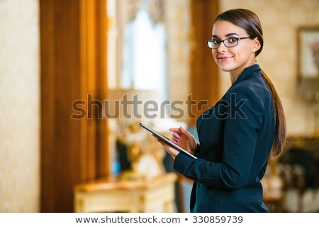 Beautiful woman using tablet in a hotel lobby Stock photo © d13