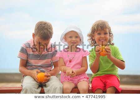 boys and girl with oranges and one liittle girl with panama hat is sitting on wooden bench. boy wear stock photo © Paha_L