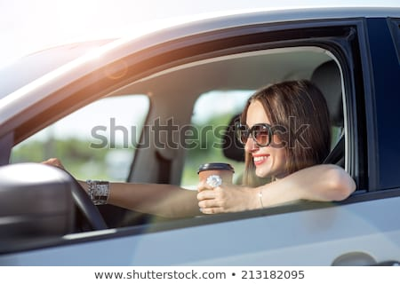Young woman with coffee to go driving her car Stock photo © vlad_star
