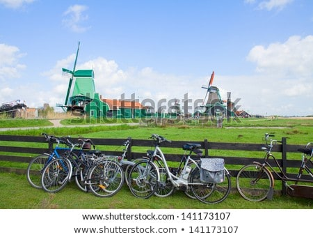 dutch windmills with bikes in zaanse schans stock photo © neirfy