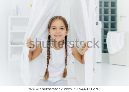 Happy European girl with two plaits, poses near clothes horse between white drying linen, poses in w Stock photo © vkstudio