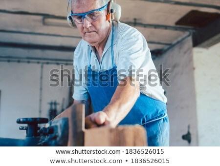 Senior carpenter working with wood planer on workpiece Stock photo © Kzenon