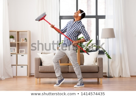 Adam kulaklık süpürge temizlik ev ev işi Stok fotoğraf © dolgachov