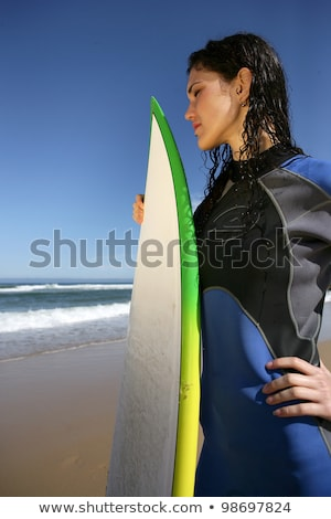 Stock photo: Brunette stood on beach with surfboard