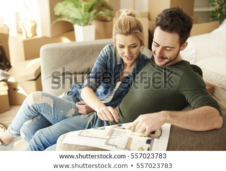 Stock photo: friends looking at a house plan