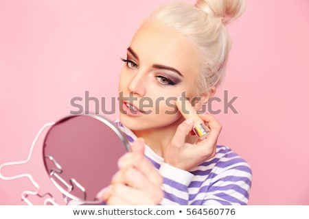Portrait of a beautiful young blonde applying makeup stock photo © dash