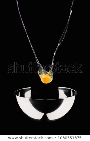 chicken egg falling into bowl isolated on black Stock photo © LightFieldStudios