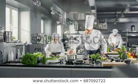 chef and cook cooking food at restaurant kitchen Stock photo © dolgachov