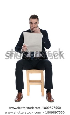 shocked elegant man sitting and reading newspaper with mouth ope Stock photo © feedough