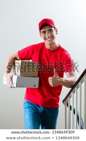 Delivery man holding mail boxes showing thumbsup Stock photo © Kzenon