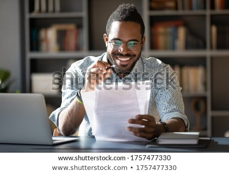 Young successful smiling teacher checking papers of students in cafe Stock photo © pressmaster