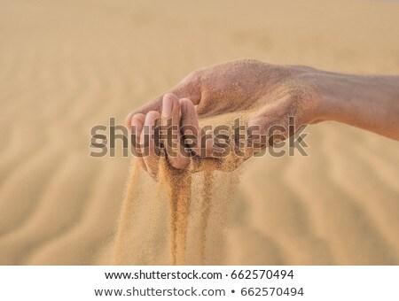 Desert, sand puffs through the fingers of a man's hand Stock photo © galitskaya