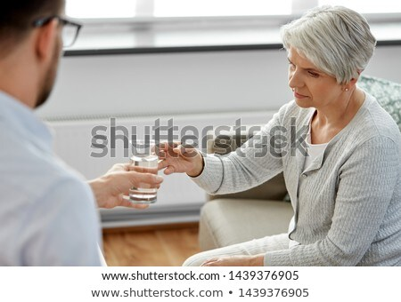 psychologist giving glass of water to senior woman Stock photo © dolgachov