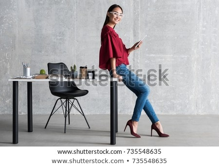 A young girl is standing leaning on a table in the office. Stock photo © Traimak