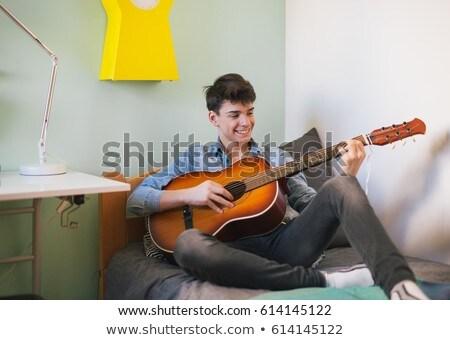 Teenage boy playing his  guitar stock photo © boggy