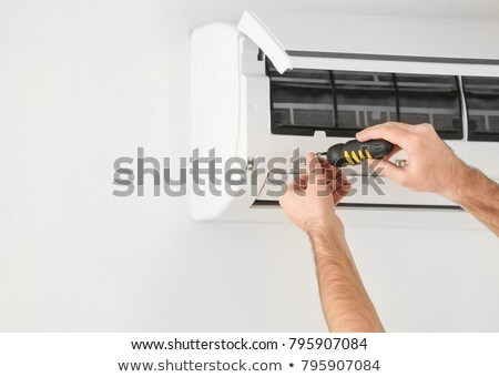 Male Technician Fixing Air Conditioner On Wall Stock photo © AndreyPopov