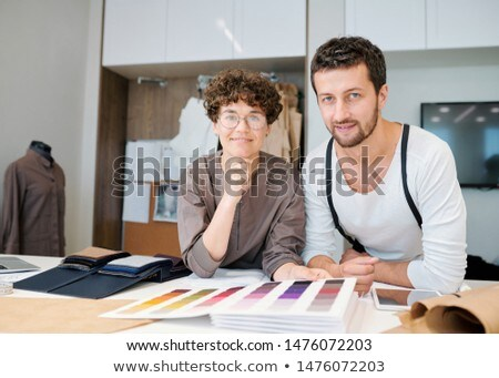 Young friendly fashion designers looking at you while bending over desk Stock photo © pressmaster