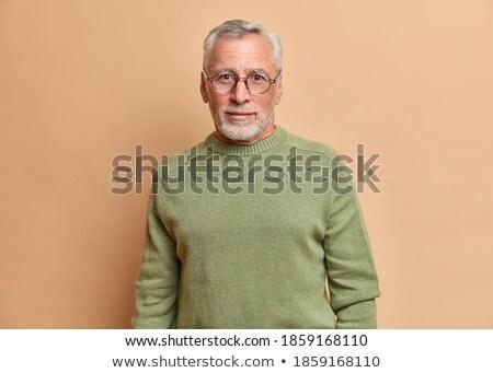 Indoor shot of handsome unshaven male entrepreneur wears formal shirt, tie and trousers, keeps hand  Stock photo © vkstudio