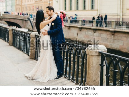 Brunette female in white dress embraces her bridegroom, looks with great love at his eyes, stand tog Stock photo © vkstudio
