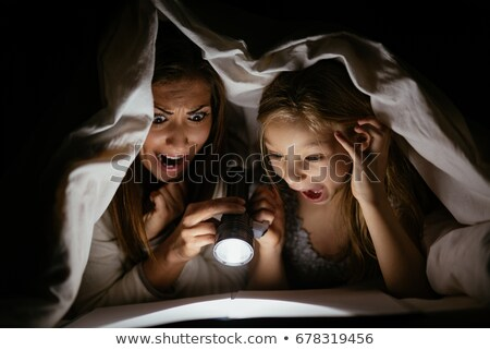 Little girl reading fairy tales book under the covers at the evening with lantern. Stock photo © Lopolo
