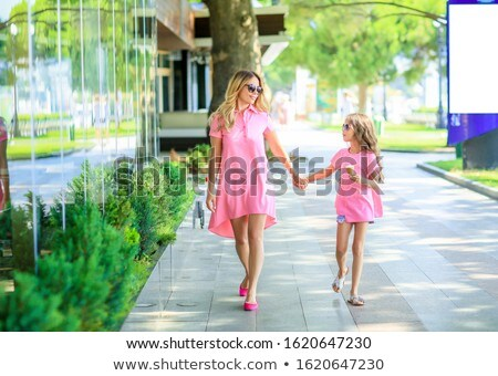 Mother with little charming daughter are sitting in the city in sunlight. mother feeds her daughter  stock photo © ElenaBatkova