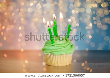green cupcake with six burning candles on table Stock photo © dolgachov