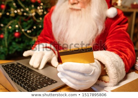 Gloved hand of Santa CLaus holding plastic credit card while making online order Stock photo © pressmaster